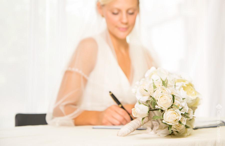 wedding photography of bride signing register